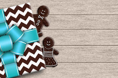Christmas present with couple gingerbread lying on wooden desk Stock Images