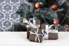 Christmas present on decorated tree background, holiday concept Stock Photo