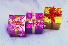 Christmas present decoration. 3 colorful gift boxes with nice ribbons on white artificial snow Stock Images