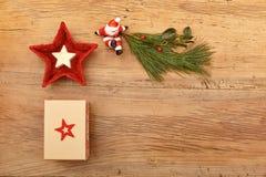 Christmas present, fir twig and Santa Claus figurine on wood stock photography