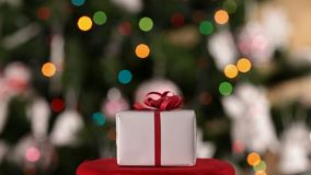Christmas present in front of decorated xmas tree stock video footage