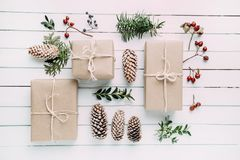 Christmas present or gift box on the wood table. Wrapped vintage craft paper gift box decorated with sprig of Christmas stock image