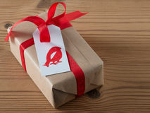Christmas present with gift tag, printed, red ribbon Stock Images