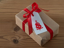 Christmas present with gift tag, printed, red ribbon Stock Photography
