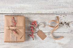 Christmas Present Gift Tags and Flowers. Top view of a Christmas present wrapped with brown paper, burlap ribbon and flowers, next to gift tag flowers and ribbon Stock Photo