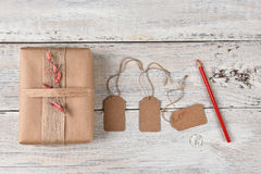 Christmas Present and Gift Tags. Top view of a Christmas present wrapped with brown paper, burlap ribbon and flowers next to gift tags and a red pencil Royalty Free Stock Image
