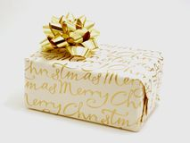Christmas present with gold bow. Christmas present wrapped  with paper bearing the wrods Merry Christmas and with a gold bow on top Stock Photography
