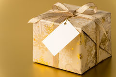 Christmas present with gold ribbon and blank tag Royalty Free Stock Photos