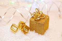 Christmas present in gold wrapping with ribbon on winter background Stock Images