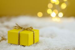 Christmas present on golden background. Christmas present in yellow wrapping paper on white artificial snow on the golden background with blurred Christmas Royalty Free Stock Images