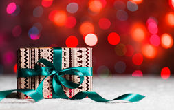 Christmas present with green bow in snow with bokeh in the background Stock Photo