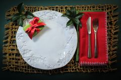 Christmas present on a handmade plate with holly sprigs and red napkin on a heavy woven mat Royalty Free Stock Images