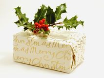 Christmas present with holly. A wrapped Christmas present bearing the words Merry Christmas with a sprig of holly on top Stock Image