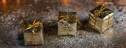 Christmas present mini golden box in the snow background banner. Close up. Christmas holiday celebration and new year concept. Win stock photo