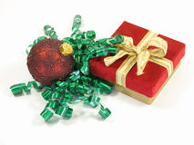Christmas present and ornament. Small christmas present wrapped with green curled ribbon and ornament isolated on white royalty free stock photography