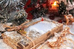 Christmas present with place for text covered with snow in the light of a red lantern on the background of New Year`s scenery. Christmas and New Year Stock Photography