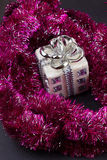 Christmas present with purple garland. A close-up Royalty Free Stock Photos