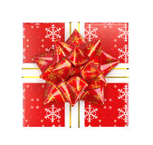 Christmas present. With red bow and gold trim on bow and white ribbon on a snowflake wrapping paper. Top view. White background for easy clipping Royalty Free Stock Image