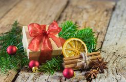 Christmas present with red ribbon bow and decoration on rustic wood royalty free stock photo