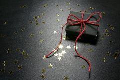 Christmas present with shiny golden stars on a black background Royalty Free Stock Images