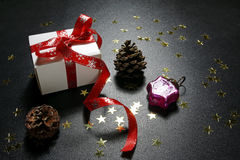 Christmas present with shiny golden stars, cones and bauble Royalty Free Stock Image