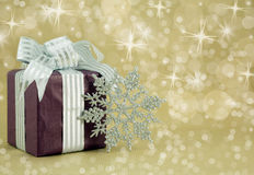 Christmas Present with silver glitter snowflake. Beautifully wrapped present with silver snowflake and gold sparkle background Stock Image