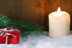 Christmas present in snow. Against blurred background with burning candle Royalty Free Stock Photography