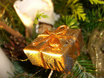 Christmas present in tree. Golden wrapped Christmas present in branches of Xmas tree Royalty Free Stock Photo