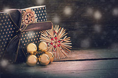 Christmas present in vintage style with straw stars and golden b. Christmas present in vintage style with decoration from straw stars and golden baubles on a Royalty Free Stock Photo