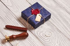 Christmas present and wax seal stamp. Creatively wrapped and decorated christmas present in box and wax seal stamp on white wooden background royalty free stock image