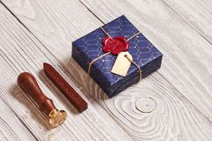 Christmas present and wax seal stamp. Creatively wrapped and decorated christmas present in box and wax seal stamp on white wooden background stock photos