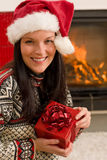 Christmas present woman Santa hat home fireplace Royalty Free Stock Image