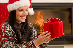 Christmas present woman Santa hat home fireplace Stock Images