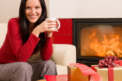 Christmas present wrap woman drink home fireplace Royalty Free Stock Images