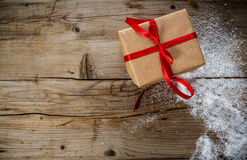 Christmas Present wrapped in craft paper on a wooden background Royalty Free Stock Images