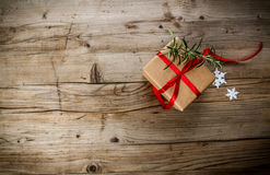 Christmas Present wrapped in craft paper on a wooden background Royalty Free Stock Photo