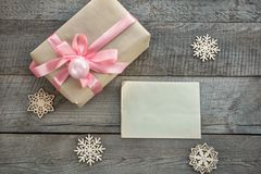 Christmas Present wrapped in paper with pink ribbon on a wooden background for a voucher coupon or  greeting card. Stock Photo