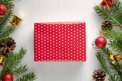 Christmas present wrapped in red paper with white polka dots. Surrounded by spruce twigs, pine cones and red and golden decorations. Flat lay style royalty free stock image