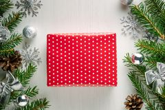 Christmas present wrapped in red paper with white polka dots. Christmas gift wrapped in red paper with white polka dots surrounded by spruce twigs, pine cones royalty free stock photography