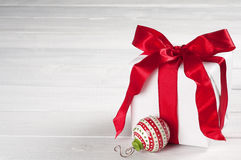 Christmas Present Wrapped in White Paper with Red Satin Ribbon and Box with ornament on gray white board background, text room Royalty Free Stock Image