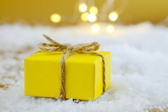 Christmas present on golden background. Christmas present in yellow wrapping paper on white artificial snow on the golden background with blurred Christmas Stock Photography