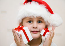 Christmas presents. The young boy has pressed beautiful gifts to both cheeks Royalty Free Stock Photos