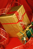 Christmas presents. Some Christmas presents with decorations and ribbon over a red background stock photos