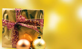 Christmas presents. With christmas balls on a gold  background Royalty Free Stock Image