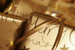 Christmas presents. Wrapped in gold paper and ribbons Stock Images