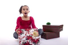 Christmas Presents. Adorable mulatto girl looking surprised and happy as she opens a gift Stock Image