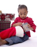 Christmas Presents. Adorable mulatto girl opening presents from her stocking royalty free stock photo