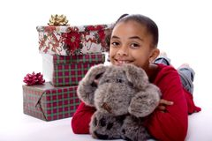 Christmas Presents. Adorable mulatto girl holding a stuffed animal in front of a pile of Christmas presents Royalty Free Stock Images