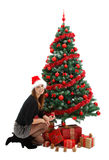 Christmas presents. Attractive young woman  with presents near the Christmas tree, wearing red santa hat Stock Photo