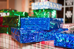 Christmas Presents. Wrapped Christmas gifts on a table with a decorated window in the background Royalty Free Stock Image